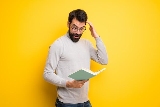 Hombre con barba y cuello alto sorprendido mientras disfruta leyendo un libro