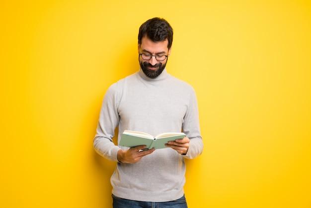 Hombre con barba y cuello alto sosteniendo un libro y disfrutando de la lectura