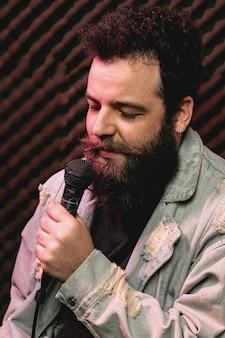 Hombre con barba elegante cantando en el micrófono