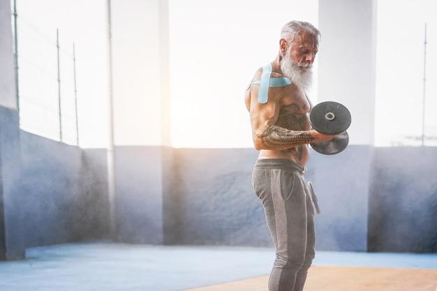 Hombre de barba fitness haciendo ejercicio de bíceps curl dentro de un gimnasio