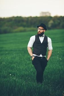Un hombre con barba y gafas de sol caminando por el campo.