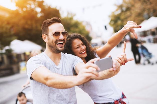 Hombre con barba y gafas de sol sonriendo mientras toma una foto con una hermosa joven.