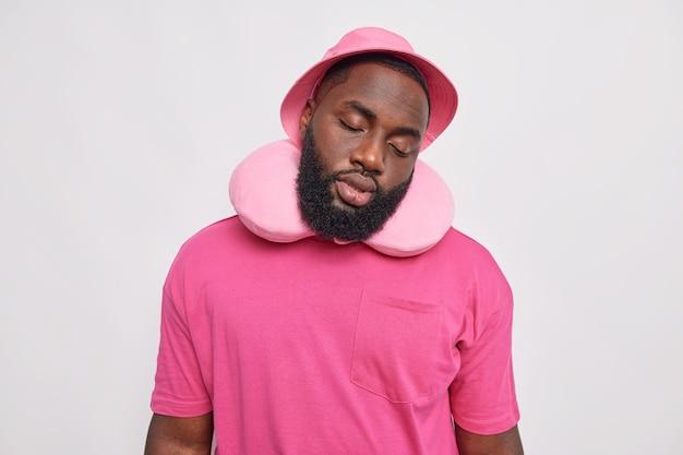 Hombre con barba gruesa inclina la cabeza viste una cómoda almohada hinchada para dormir alrededor del cuello panamá y una camiseta rosa viaja en autobús aislado sobre una pared blanca