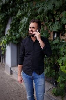 Un hombre con barba va y habla por teléfono.