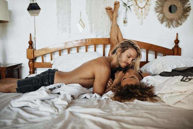 Hombre con barba incipiente y torso desnudo mira a los ojos de su amada que arrojó sus piernas contra la pared