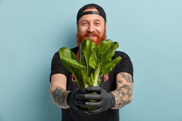 Hombre con barba de jengibre en delantal y guantes con ensalada