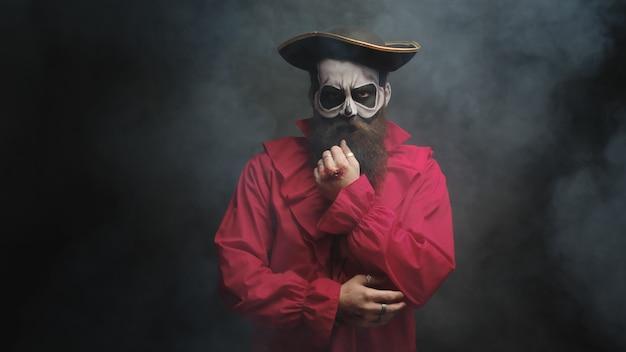 Hombre de barba larga disfrazado de pirata para halloween sobre un fondo negro con humo saliendo.