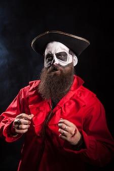 Hombre con barba larga disfrazado de pirata medieval sobre fondo negro para halloween.