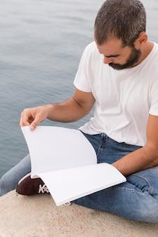 Hombre con barba leyendo libro junto al lago