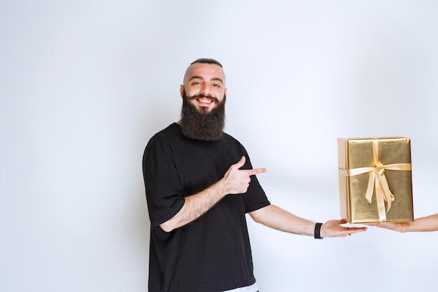 Hombre con barba mostrando su caja de regalo de envoltura dorada.