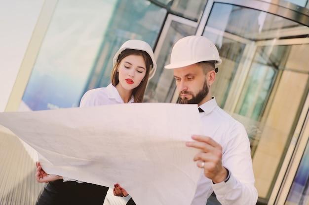 Un hombre con barba y una mujer en ropa de negocios está estudiando dibujos y documentos para un nuevo proyecto.