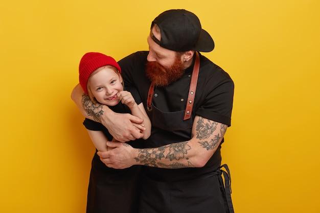 Hombre con barba pelirroja en delantal con hija