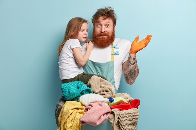 Hombre con barba pelirroja lavando ropa y sosteniendo a su hija