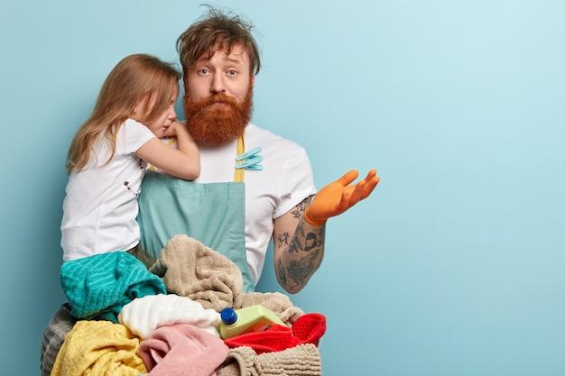 Hombre con barba pelirroja sosteniendo a su hija y lavando ropa