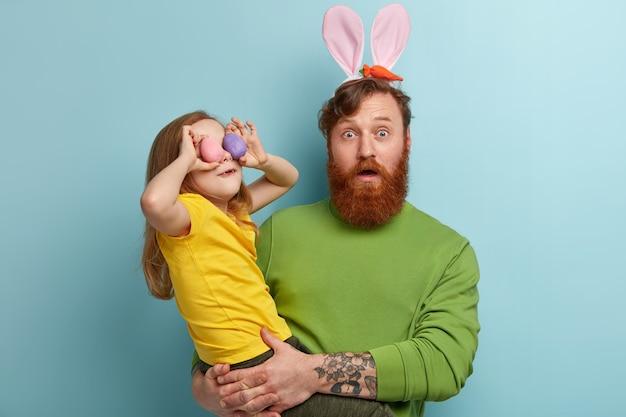 Hombre con barba pelirroja vistiendo ropas coloridas y orejas de conejo sosteniendo a su hija