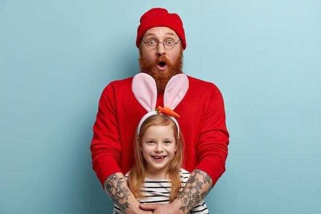 Hombre con barba pelirroja vistiendo ropas coloridas y sosteniendo a su hija