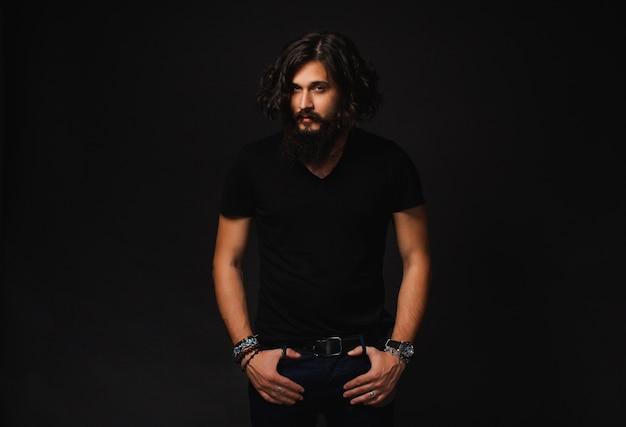 Hombre con barba y pelos largos con las manos en los bolsillos