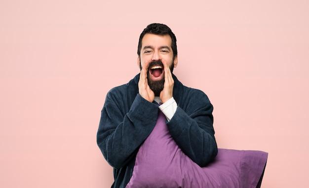 Hombre con barba en pijama gritando y anunciando algo sobre fondo rosa aislado