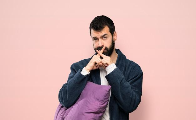 Hombre con barba en pijama que muestra un signo de gesto de silencio sobre fondo rosa aislado