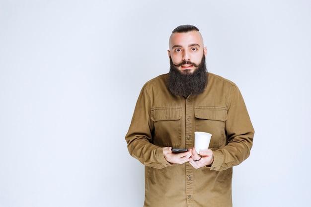 Hombre con barba revisando sus mensajes mientras toma un café.