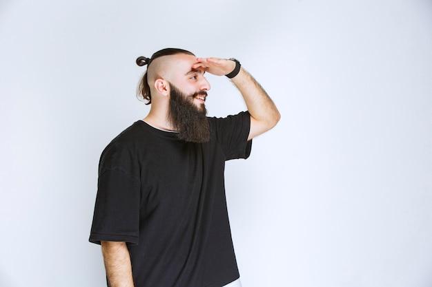 Hombre con barba saludando a sus amigos.