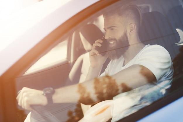 El hombre con barba se sienta al volante de un vehículo eléctrico.