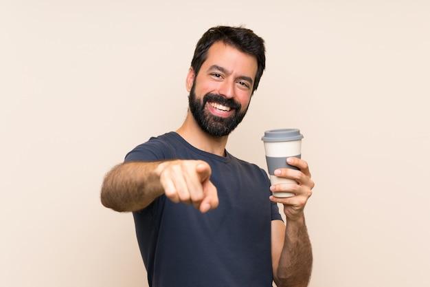 Hombre con barba sosteniendo un café apunta con el dedo con una expresión segura