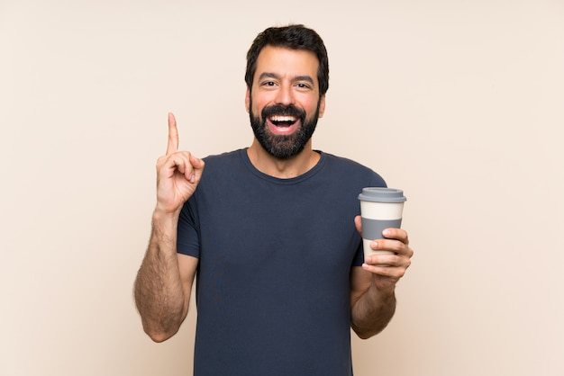 Hombre con barba sosteniendo un café apuntando hacia una gran idea