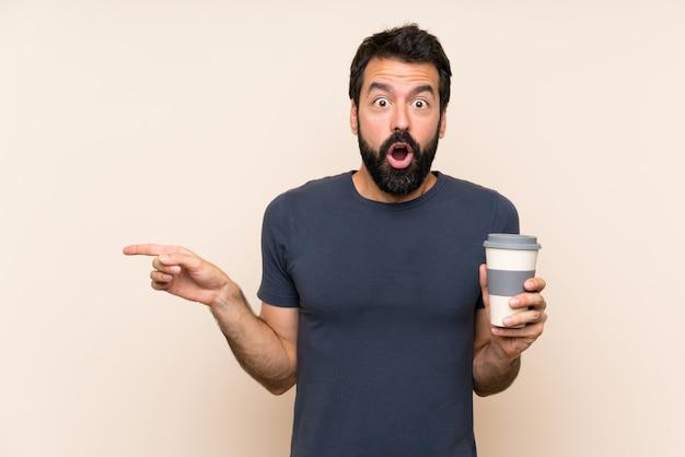 Hombre con barba sosteniendo un café sorprendido y apuntando hacia el lado