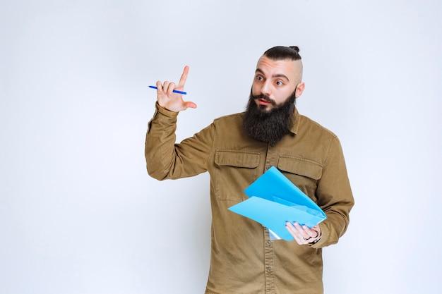 Hombre con barba sosteniendo un cuestionario y parece confundido y pensativo.