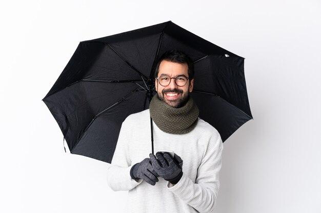 Hombre con barba sosteniendo paraguas sobre pared aislada