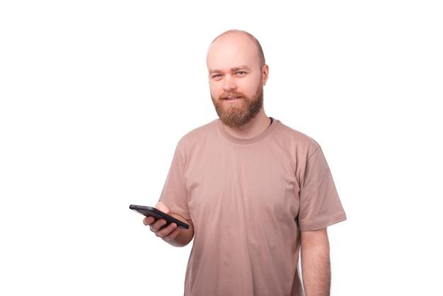 Hombre con barba sosteniendo smartphone y mirando a la cámara en blanco
