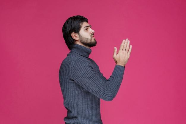 Hombre con barba sosteniendo sus manos de una manera como si estuviera rezando o deseando algo.