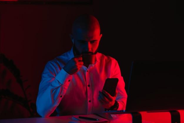 Un hombre con barba está trabajando de forma remota en una computadora portátil en casa. un tipo con auriculares está tomando café y leyendo las noticias. un empleado frente a la computadora en los rayos de luz azul y roja.