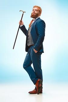 El hombre con barba en un traje con bastón.