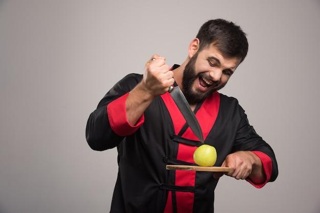 Hombre con barba tratando de cortar una manzana sobre tabla de madera.