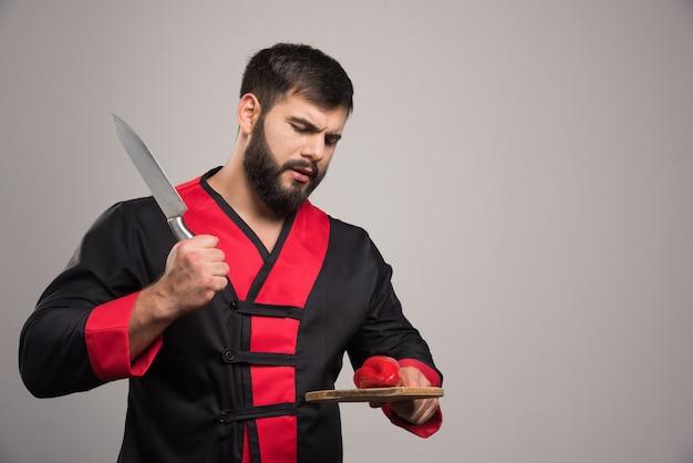 Hombre con barba tratando de cortar un pimiento rojo sobre tabla de madera.