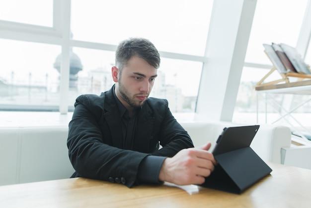 Un hombre con barba usa una tableta en un hermoso café ligero. un hombre de negocios mira la tableta en un almuerzo.