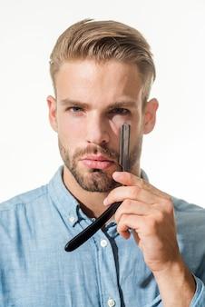 Hombre barbero con barba y bigote sostiene peluquería de navaja recta demostrando de barbería