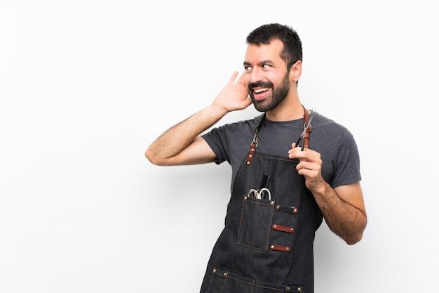 Hombre barbero en un delantal escuchando poniendo la mano en la oreja