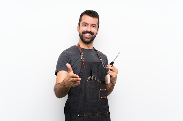 Hombre barbero en un delantal estrechándole la mano por cerrar un buen trato