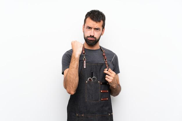 Hombre de barbero en un delantal con gesto enojado