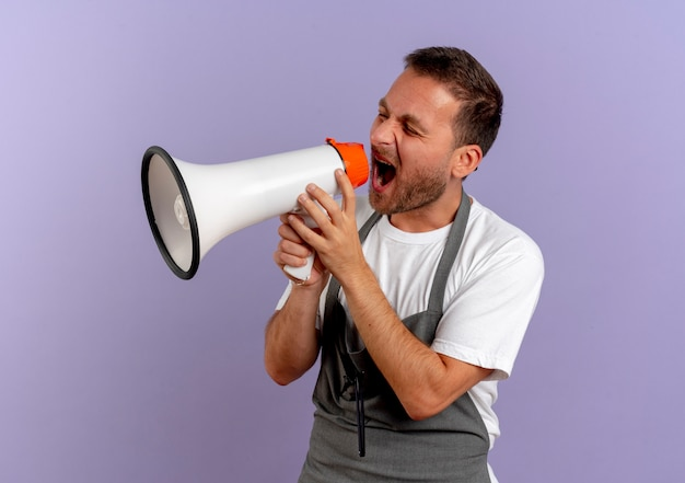 Hombre barbero en delantal gritando al megáfono con expresión agresiva de pie sobre la pared púrpura