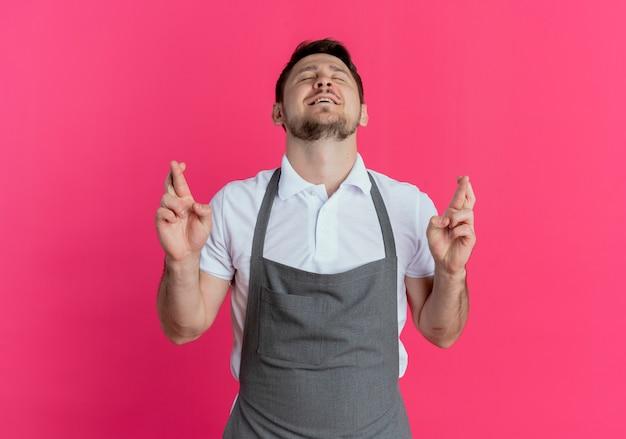 Hombre barbero en delantal haciendo deseo deseable cruzar los dedos con los ojos cerrados de pie sobre la pared rosa