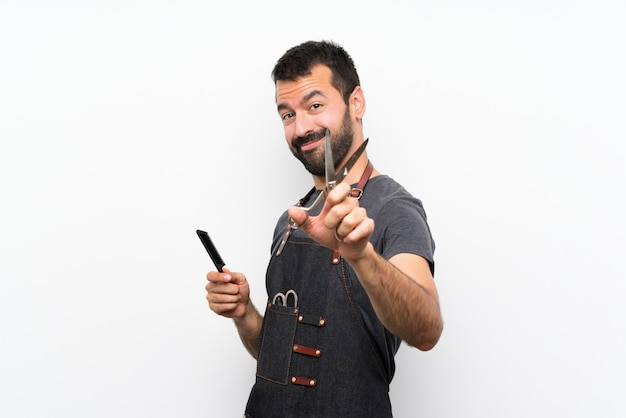Hombre de barbero en un delantal sobre pared blanca aislada