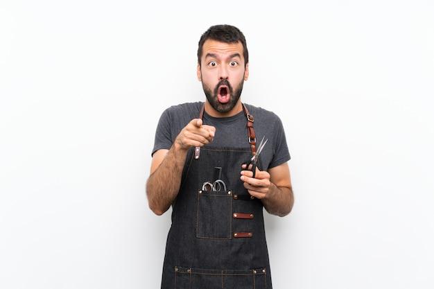 Hombre barbero en un delantal sorprendido y apuntando al frente