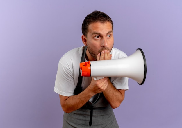 Hombre barbero en delantal sosteniendo megáfono mirando a un lado sorprendido cubriendo la boca con la mano de pie sobre la pared púrpura