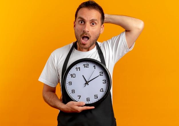 Hombre barbero en delantal sosteniendo reloj de pared mirando hacia el frente preocupado de pie sobre la pared naranja