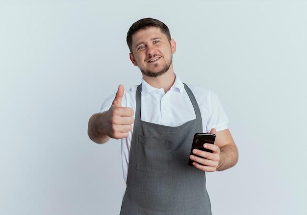 Hombre barbero en delantal sosteniendo smartphone mostrando pulgares arriba sonriendo con cara feliz de pie sobre la pared blanca