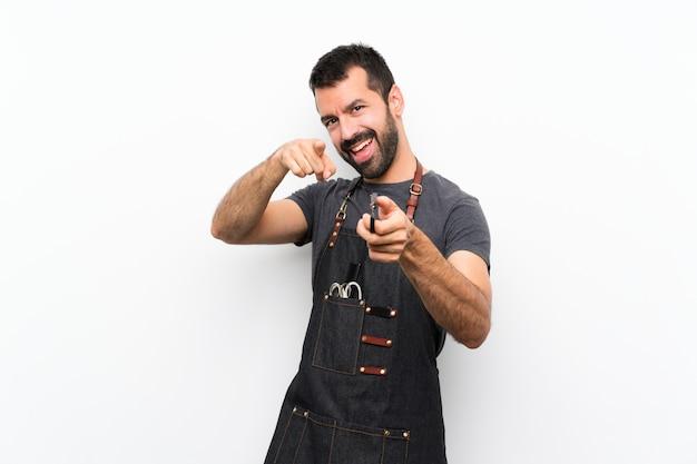 El hombre del barbero en un delantal te señala con el dedo mientras sonríe